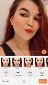 Print de uma selfie de uma mulher com cabelos vermelhos mostrando a ferramenta Relight do AirBrush