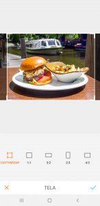 Hambúrguer em cima de um prato branco com batatas fritas de acompanhamento usando a ferramenta de cortar do AirBrush.
