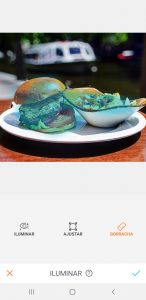 Hambúrguer em cima de um prato branco com batatas fritas de acompanhamento usando a ferramenta Iluminar do AirBrush.