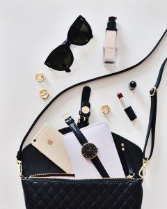 Foto de uma bolsa aberta com vários acessórios de fora como óculos de sol, batom, relógio, celular, etc.