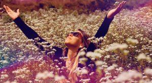 foto de uma mulher com braços abertos em um campo cheio de flores dente de leão