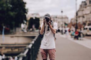 Um homem segurando uma máquina fotográfica como se fosse tirar uma foto com o resultado final da edição