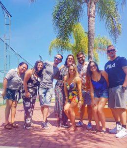 foto de amigos reunidos em frente a um coqueiro