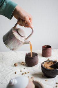 Foto de uma mesa posta e um café sendo despejado em uma xícara.