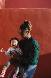 Foto de um pai segurando um bebê risonho.
