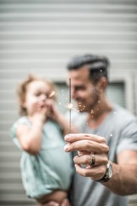 Pai segurando seu filho com uma vela na mão