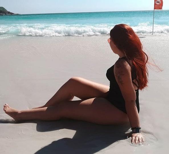 MUlher sentada na areia da praia olhando para o mar