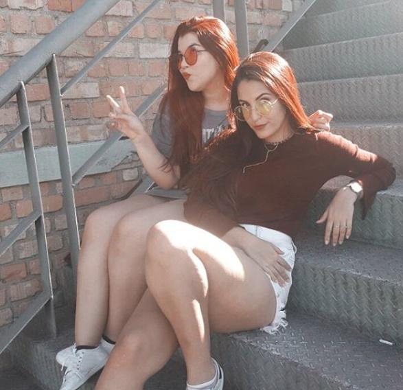 Duas amigas sentada em um escada posando para a foto