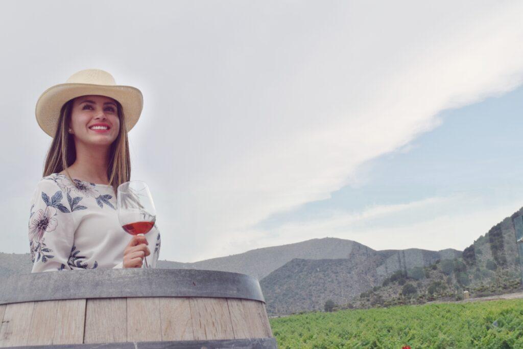 mujer con sombrero rojo y abanico rojo en terraza con montañas detrás