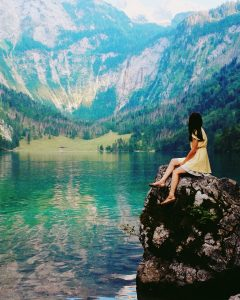 Foto de uma mulher sentada em uma rocha com uma paisagem com montanhas e lago ao fundo com o resultado final da edição
