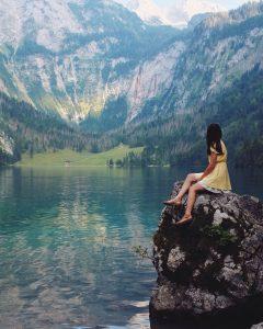 Foto de uma mulher sentada em uma rocha com uma paisagem com montanhas e lago ao fundo.