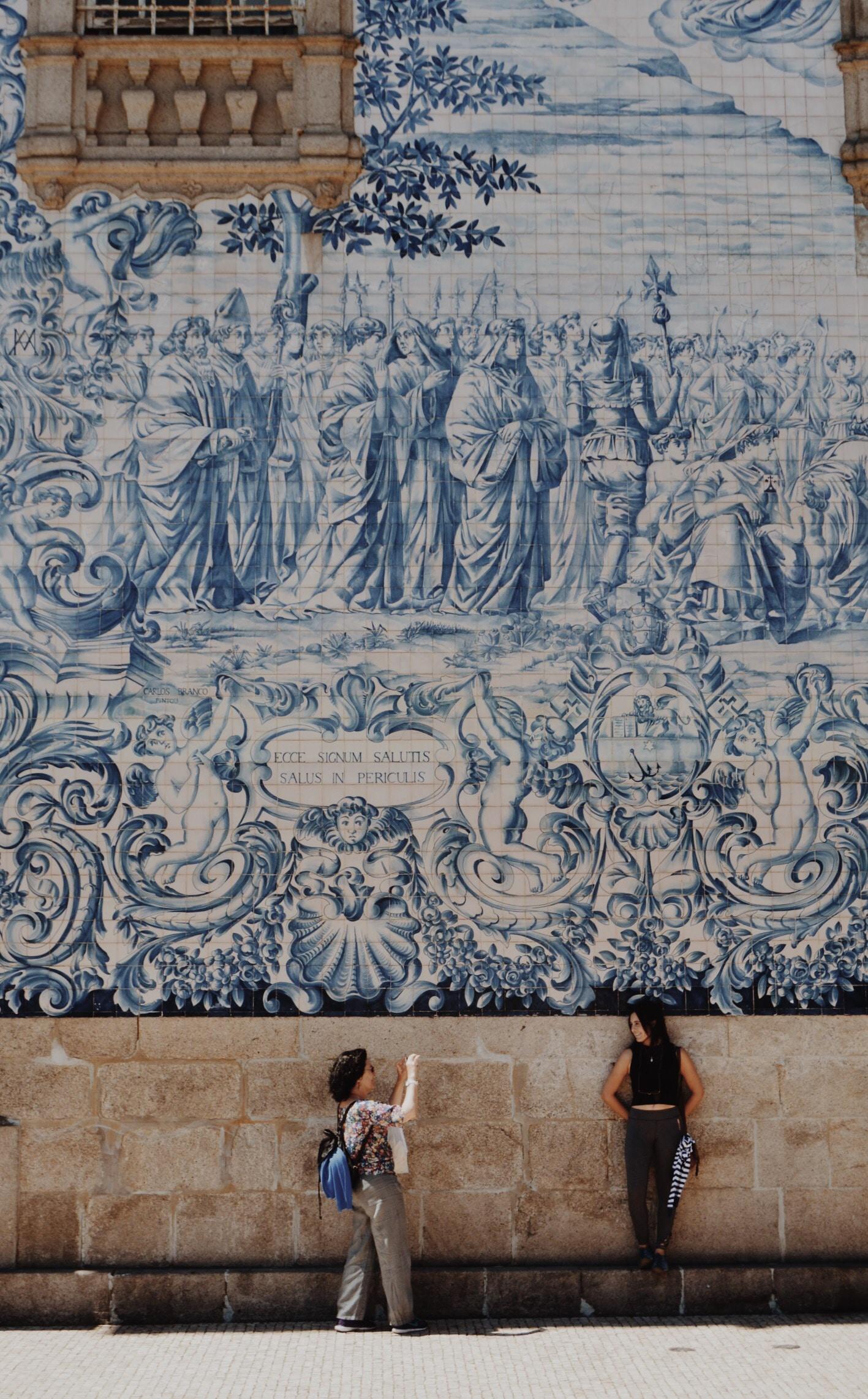 Foto de duas mulheres posando em uma parede com uma arte. Uma está tirando a foto da outra.