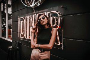 """Foto de uma mulher posando em frente a uma placa escrito """"Diner"""" com edição final."""