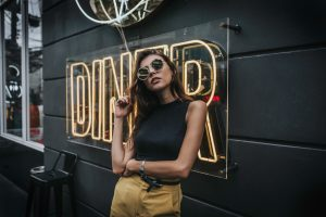 """Foto de uma mulher posando em frente a uma placa escrito """"Diner"""""""