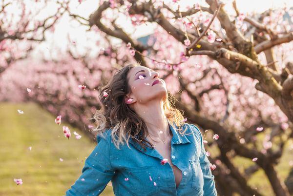 foto de uma mulher loira olhando para cima perto de uma árvore cm flores