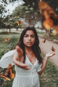 Uma mulher estendo a mão com uma edição de borboletas voando ao redor dela.