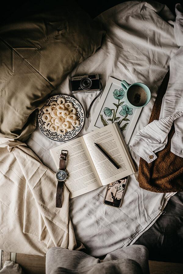 Foto de vários objetos espalhados na cama. Relógio, máquina fotográfica, livro, caneta, celular e café.