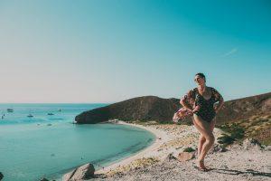 Uma mulher posando com uma paisagem de praia de fundo