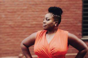 Uma mulher negra posando olhando para o lado com as mãos na cintura