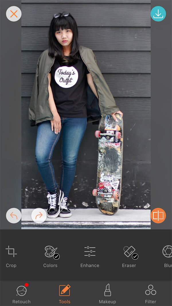 """woman in black tshirt with slogan """"Today's Outfit holds skateboard in front of black wall"""