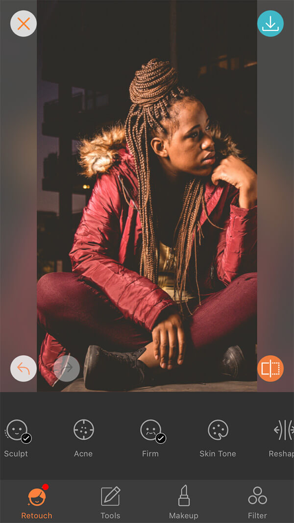 woman with braids in red jacket and pants sits in front of dark background