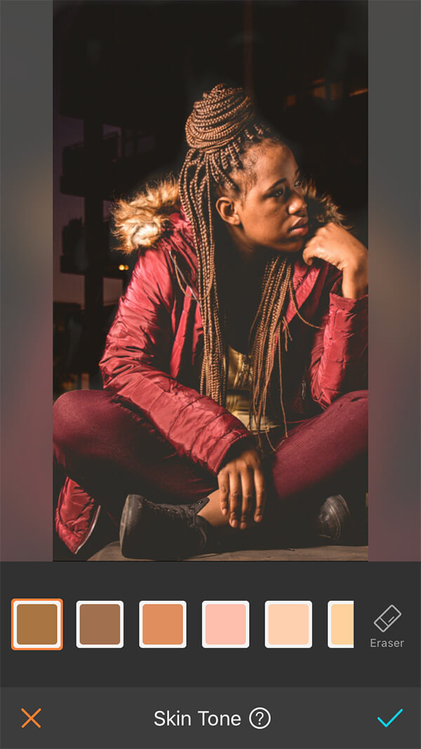 woman with braids in red jacket and pants sits in front of dark city background
