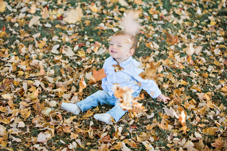 menino brincando com as folhas amarelas do outono