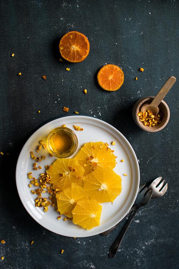 foto de um prato com laranjas num fundo preto