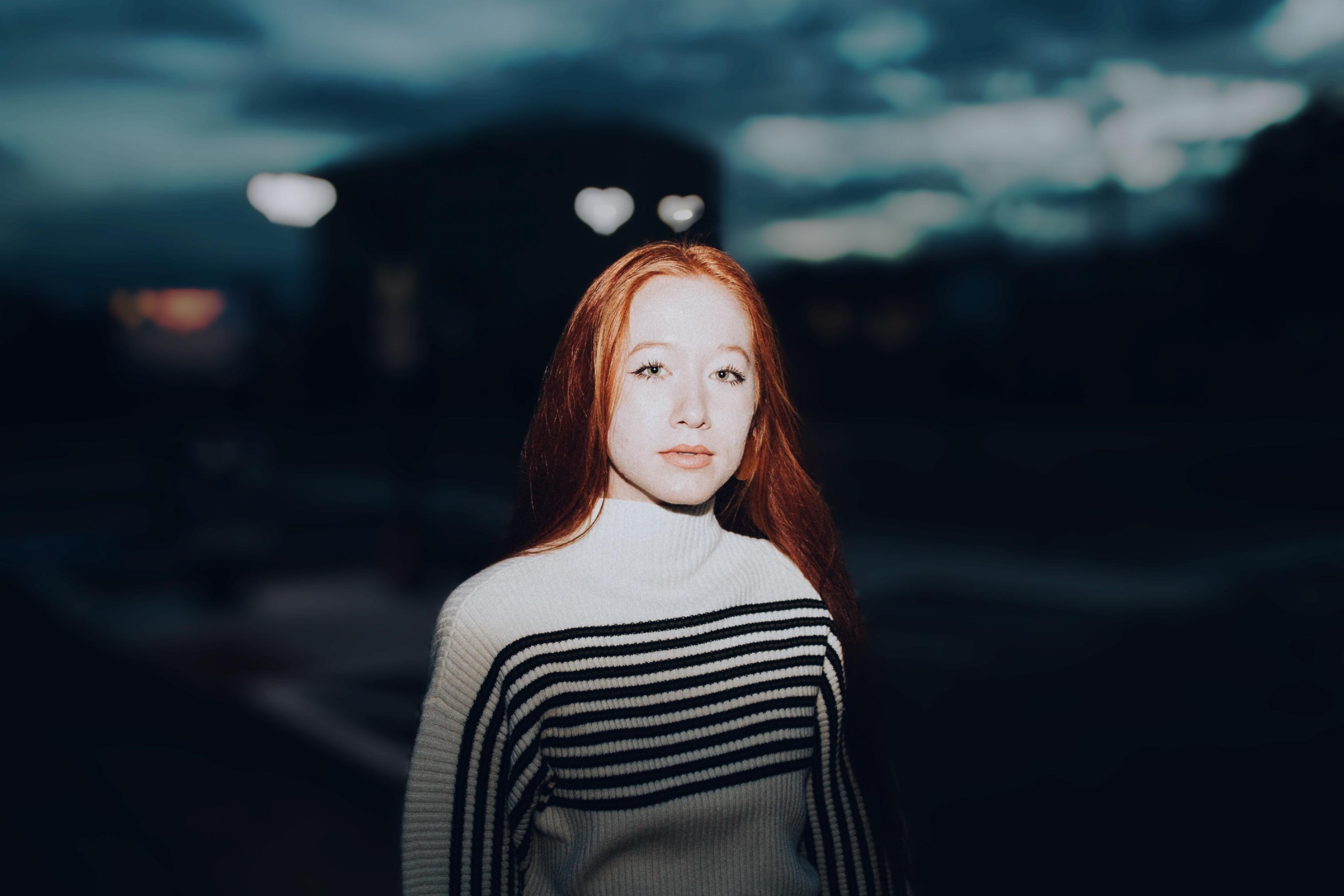 menina ruiva em frente a um flash