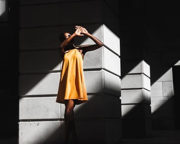uma mulher de amarelo entre paredes com sombras