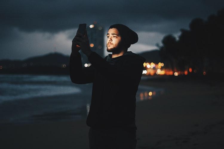 retrato de um homem a noite mexendo no celular