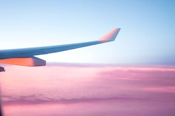 asa de avião nas nuvens rosas e céu azul
