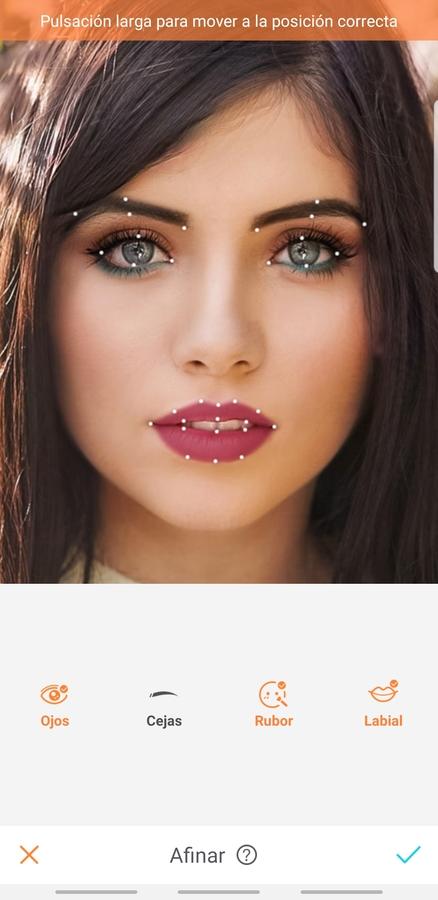 Mujer con cabello largo oscuro y ojos azules, con un árbol de flores rosas detrás de ella. Tiene un maquillaje muy colorido con azul en los ojos y labios violeta.