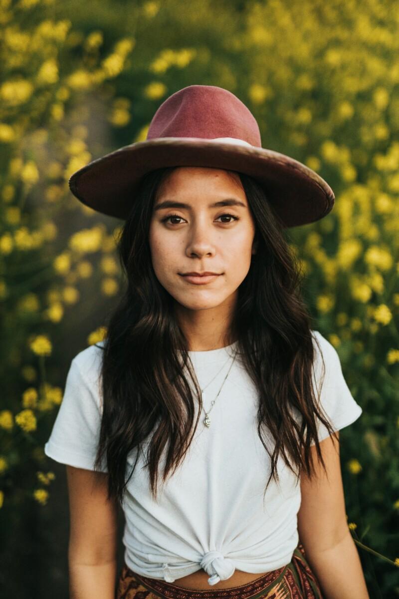mujer con sombrero y playera blanca