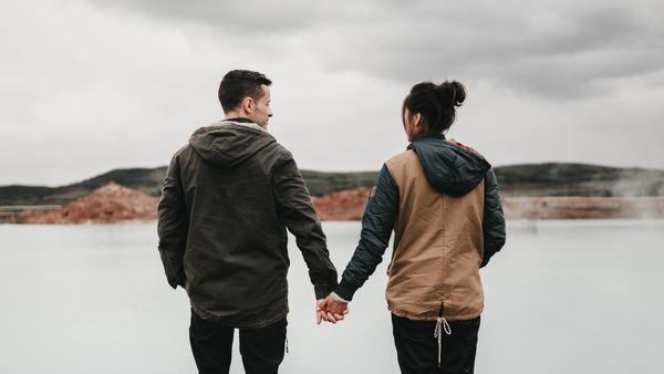 pareja agarrándose de las manos y viendo al agua congelada
