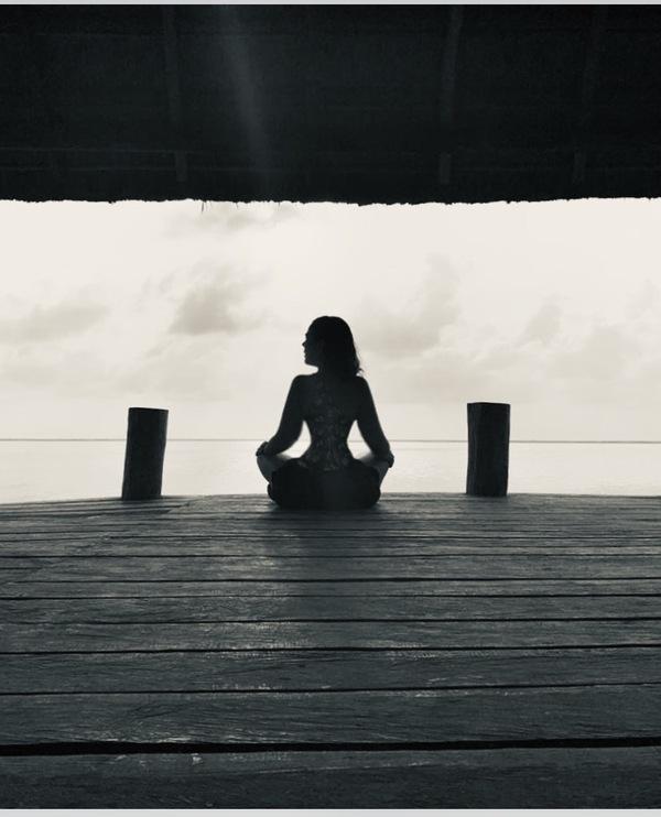 mujer meditando en una cabaña al aire libre