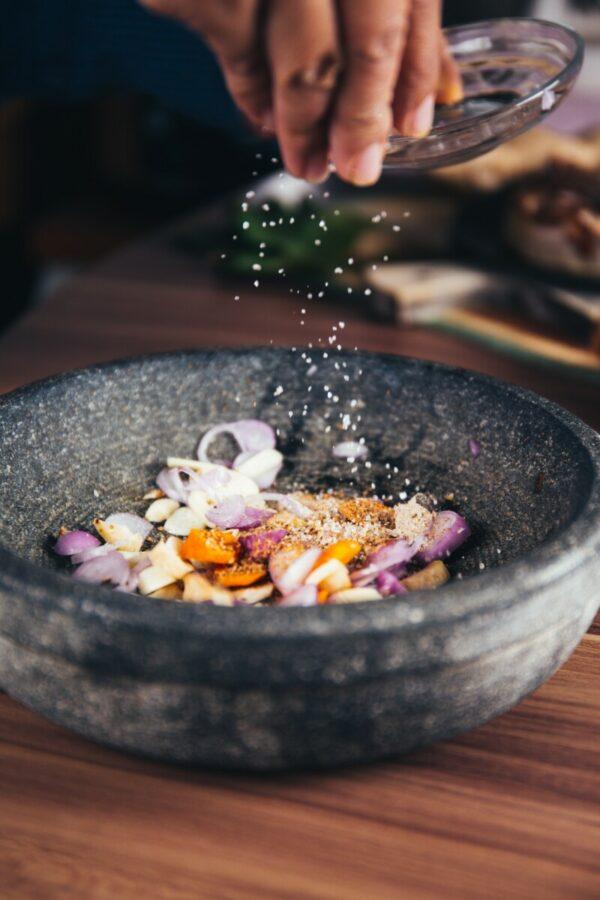 foto de uma pessoa jogando sal em um pilão com flores comestíveis