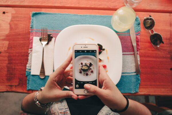foto tirada de cima mostrando a tela de um celular tirando foto de um prato de comida