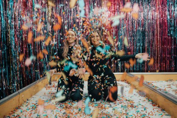 Foto de duas amigas comemorando com papéis picadas caindo sob elas