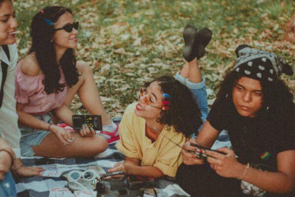 Foto de um grupo de amigos conversando enquanto estão deitados e sentados na grama