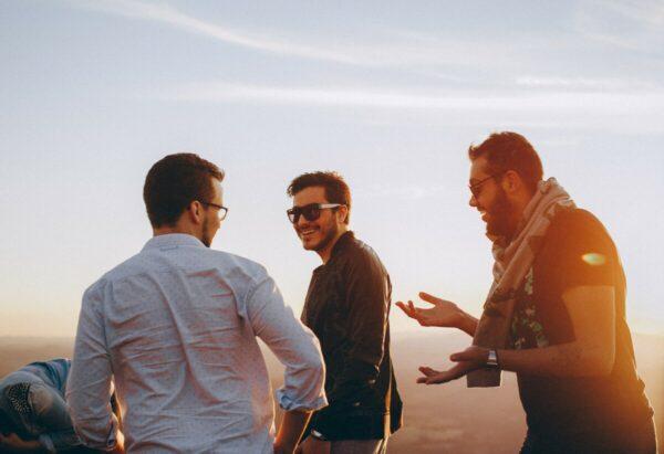 Foto de três amigos juntos e rindo durante um pôr-do-sol
