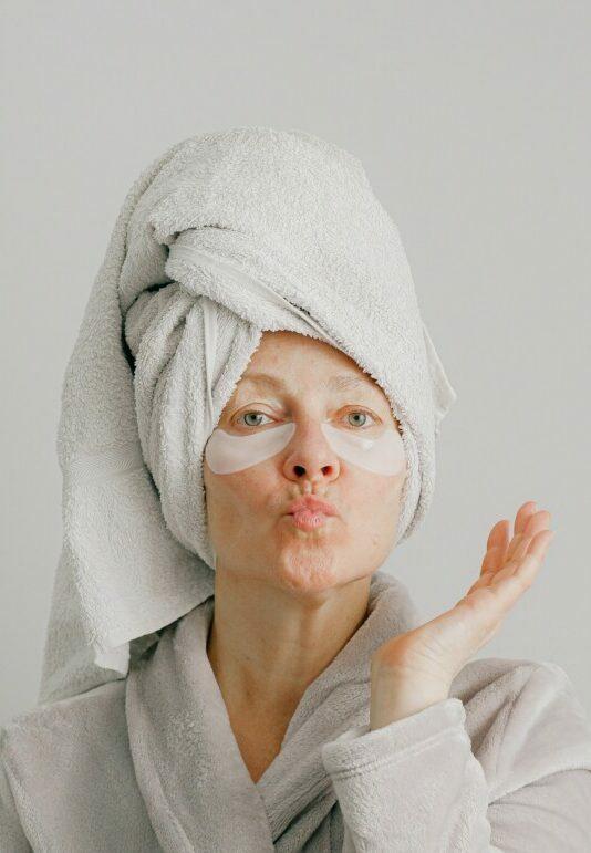Foto de uma senhora com toalha enrolada no cabelo, mandando beijinho para a câmera fazendo skin care.