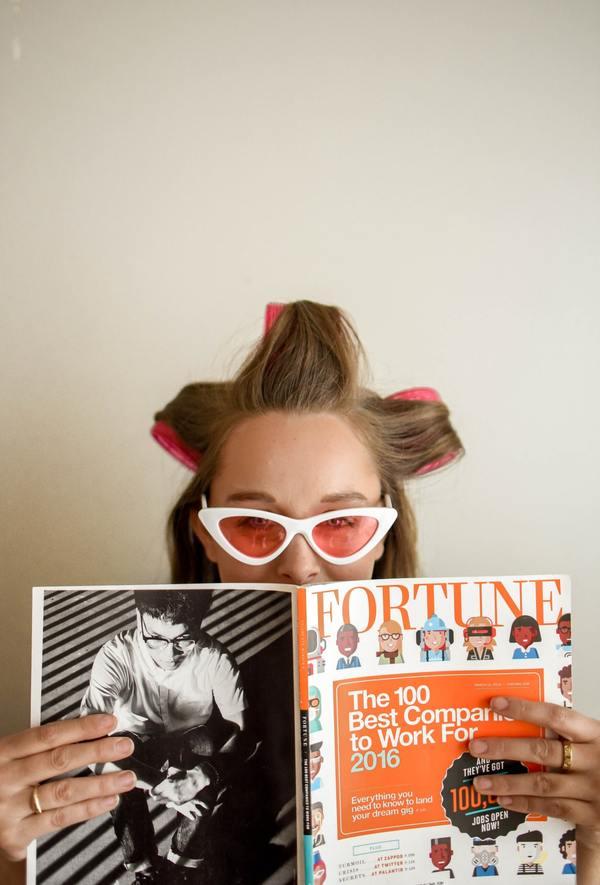 mujer con tubos en la cabeza, lentes de sol y una revista