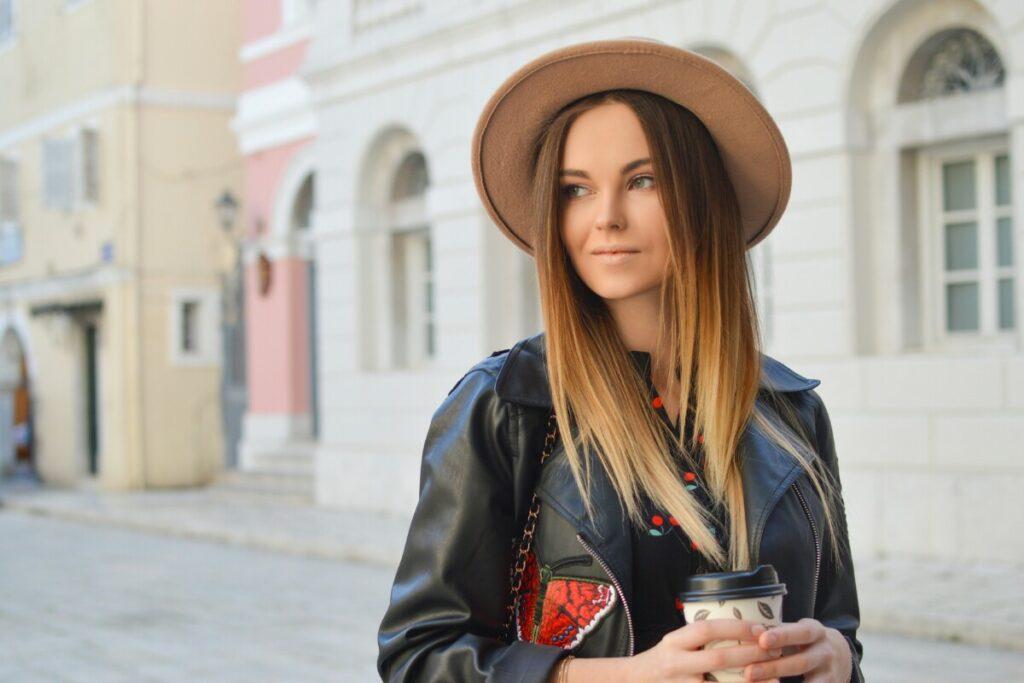 mujer de cabello lacio y rubio tomando un café