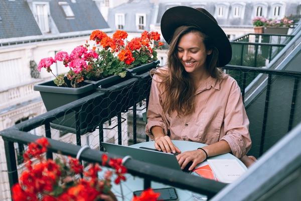 mujer rubia con sombrero trabajando en un balcón en Paris