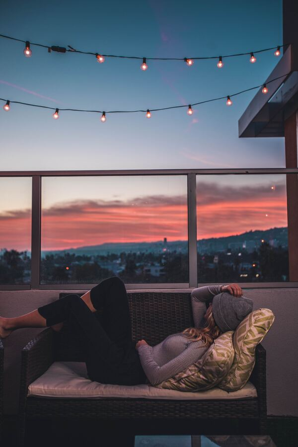 mujer en un balcón al atardecer