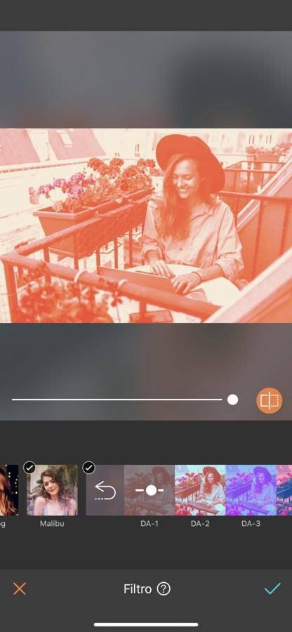 mujer rubia con sombrero trabajando en un balcón en Paris. La imagen tiene un filtro naranja.