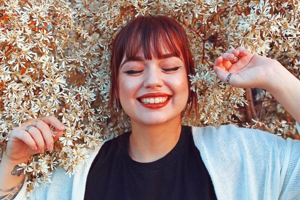 mujer acostada en una cama de flores sonriendo