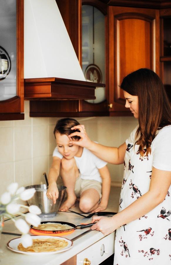 Mamá en la cocina cocinando junto con su hijo varón de 5 años. La foto ha sido editada con AirBrush