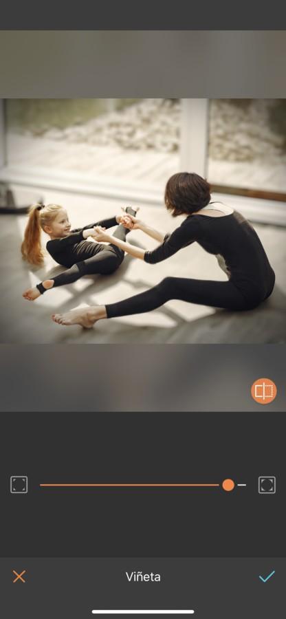Foto de mamá practicando ballet o gimnasia con su hija. Ambas están vestidas con un payasito negro y están haciendo estiramientos.